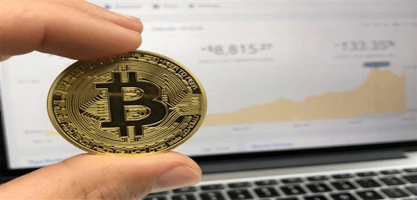 Bitcoin zwischen Fingern vor einem Laptop-Screen mit Kursen