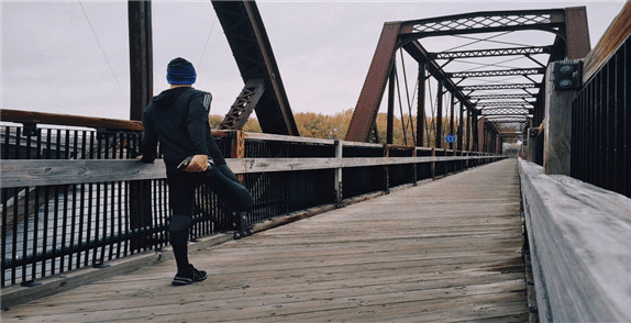 Jogger dehnt sich an der Brücke. Trading erfordert Fitness, physich und geistig