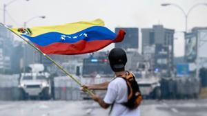 personne tenant un drapeau du Venezuela